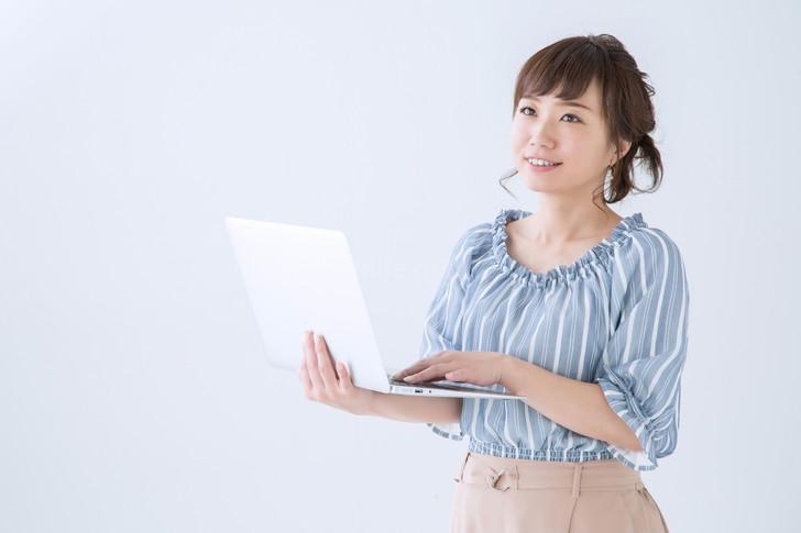 パソコンを持つ笑顔の女性