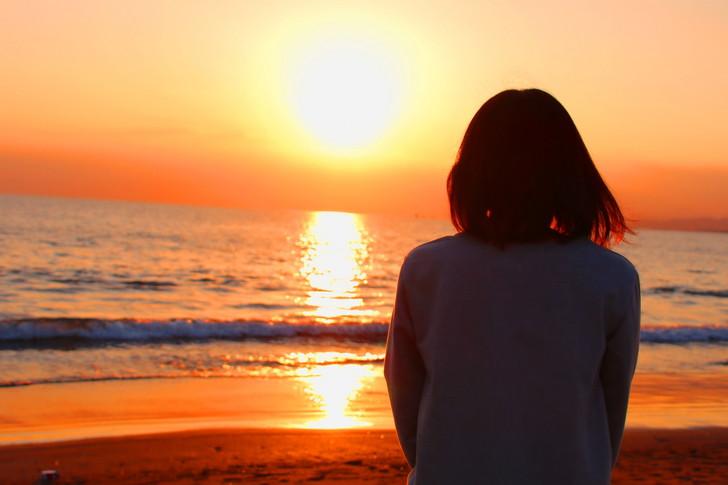 夕日と海を眺める女性