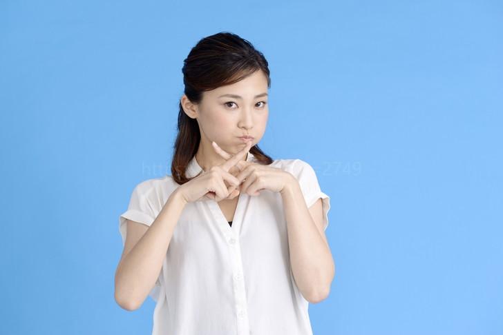 バツ印を指でつくる女性
