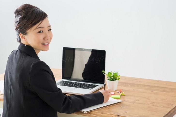 パソコンとメモ帳を用意する女性