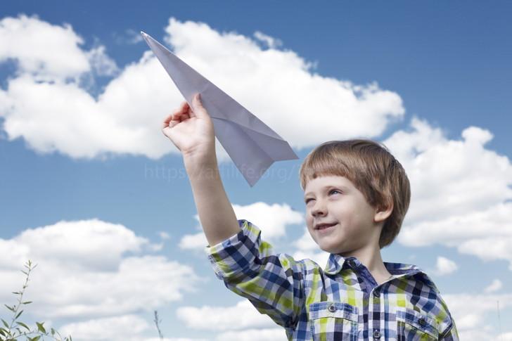紙飛行機を飛ばす子供