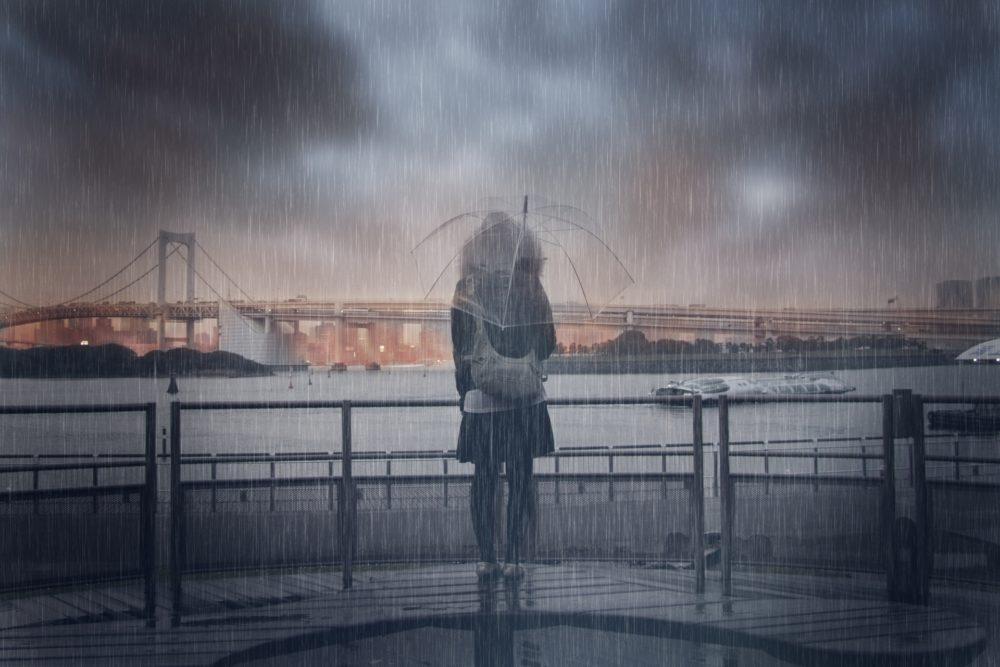 雨の中たたずむ女性